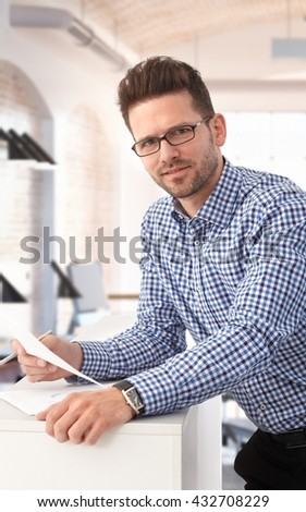 Portrait of smart young businessman working at office. - stock photo