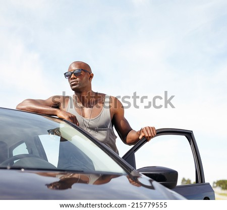 Portrait of smart young man leaning on car. African male model wearing sunglasses standing by his car looking away with door open outdoors. - stock photo