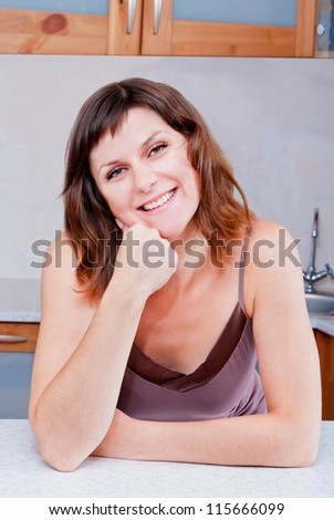 Portrait of smart young woman standing at the kitchen - stock photo