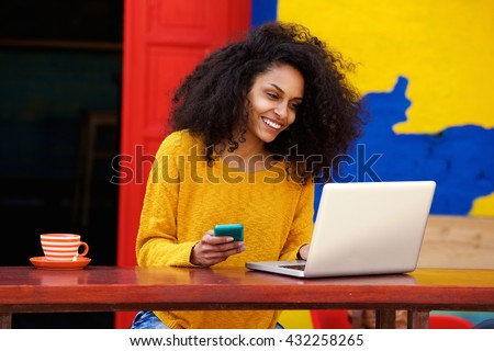 Portrait of smart young woman with mobile phone working on laptop at outdoor coffee shop - stock photo