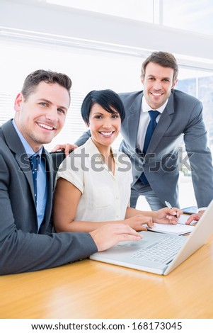 Portrait of smartly dressed young colleagues using laptop at office desk