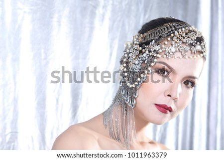 Portrait of Smile Asian Woman in Fashion make up Style accessories on head black hair, studio lighting silver fabric background copy space, Concept luxury to join social night event