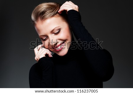 portrait of smiley and beautiful woman against dark background - stock photo