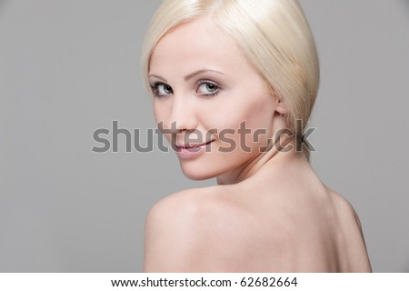 portrait of smiley beautiful blonde over grey background
