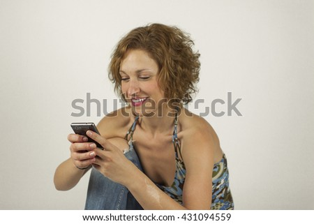 Portrait of smiley casual beautiful woman in jeans with the phone shoot in studio, isolated on a white background