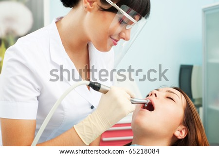 portrait of smiley dentist in mask and patient - stock photo