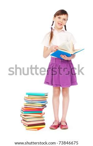 portrait of smiley schoolgirl standing near books - stock photo
