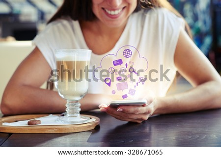 portrait of smiley young woman sitting in cafe and using her smartphone. virtual icons floating in the air - stock photo