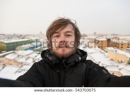 Portrait of smilig guy with beard on a rooftop