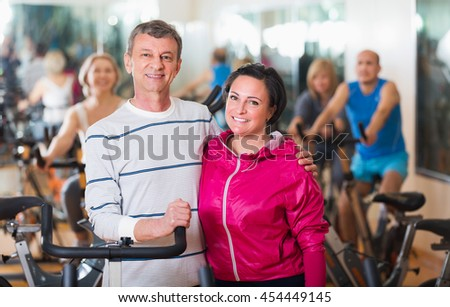 Portrait of smiling active elderly couple exercising in gym