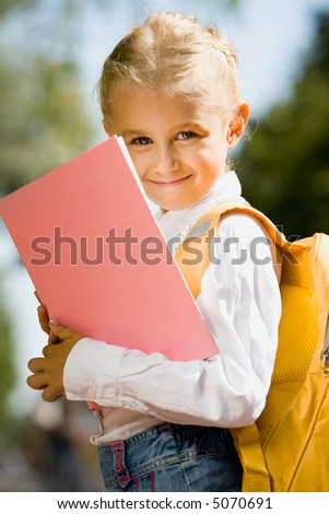 Portrait of smiling adorable girl with backpack holding a book outside - stock photo
