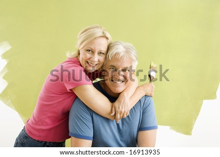 Portrait of smiling adult couple sitting in front of half-painted wall with paintbrushes.