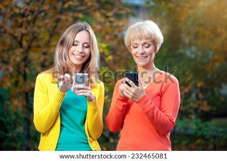 Portrait of smiling adult girl and her pretty middle aged blonde mother playing smart phones outdoors - stock photo