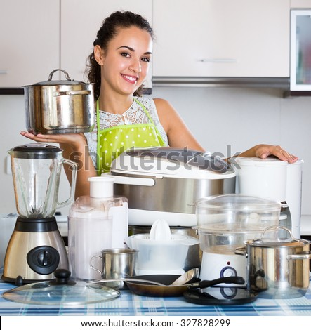 Portrait of smiling adult girl with kitchen appliances at home - stock photo