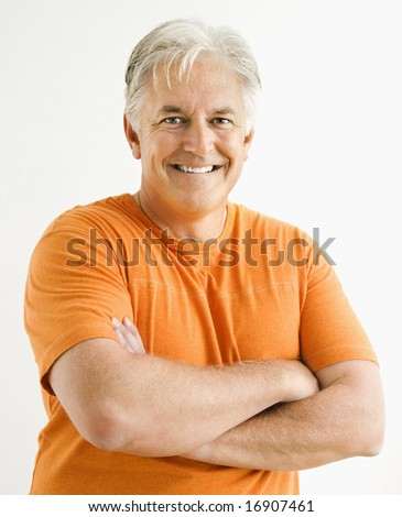 Portrait of smiling adult man standing looking at viewer with arms crossed. - stock photo