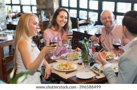 Portrait of smiling adults having dinner in family restaurant. Focus on blonde girl - stock photo
