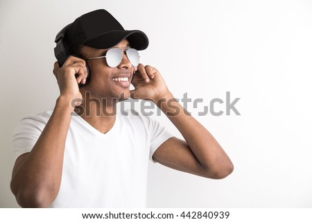 Portrait of smiling african american guy in cap and sunglasses listening to music with headphones on light background - stock photo
