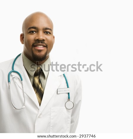 Portrait of smiling African-American man doctor wearing uniform standing against white background. - stock photo