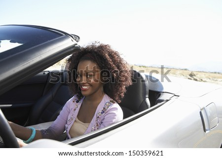 Portrait of smiling African American woman driving convertible on desert road - stock photo