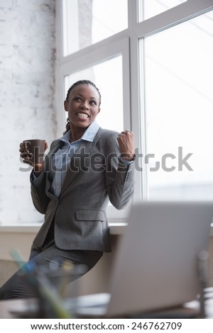Portrait of smiling african business woman at her office with coffee cup celebrating success and expressing happiness joy and positivity - stock photo