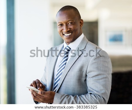 portrait of smiling african businessman using smart phone in office - stock photo