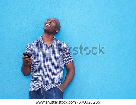 Portrait of smiling african man with a mobile phone standing against blue background  - stock photo