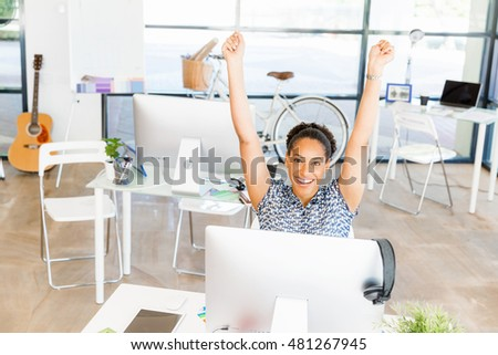Portrait of smiling afro-american office worker in offfice holding her arms up