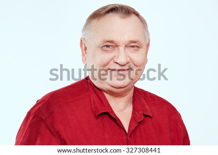 Portrait of smiling aged man wearing red shirt against white background - retirement concept - stock photo