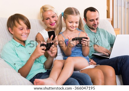 Portrait of smiling american family playing with gadgets at home