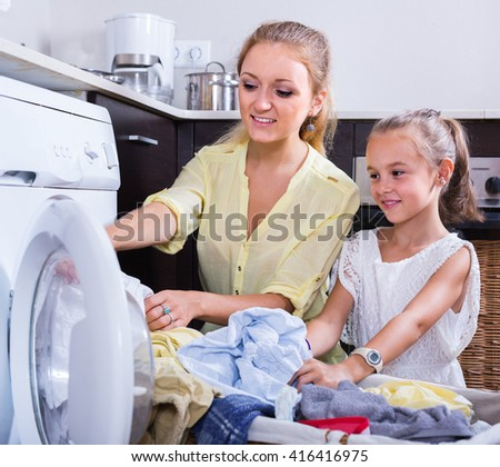 Portrait of smiling american mom and daughter with bin near washing machine