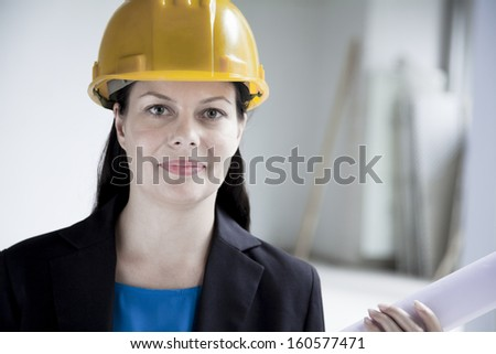 Portrait of smiling architect in hardhat holding rolled up blueprint  - stock photo