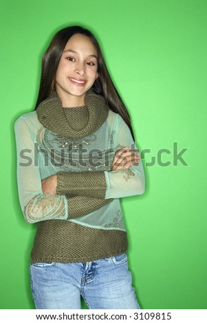 Portrait of smiling Asian-American teen girl with arms crossed standing in front of green background. - stock photo