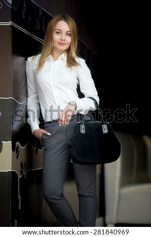 Portrait of smiling attractive confident young business woman in smart casual office wear leaning against the wall - stock photo