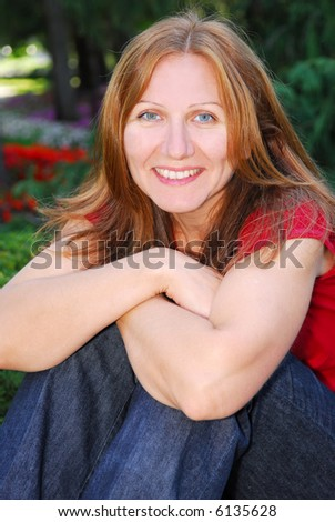 Portrait of smiling attractive mature woman relaxing in summer park - stock photo