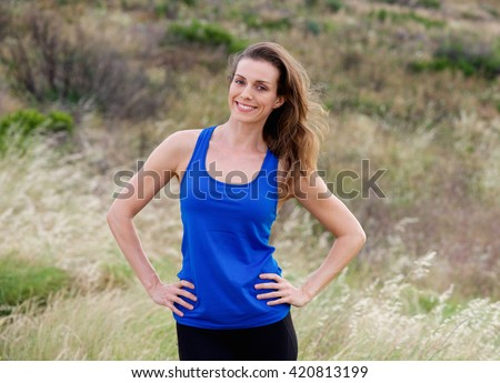 Portrait of smiling attractive  woman with blue tank top - stock photo