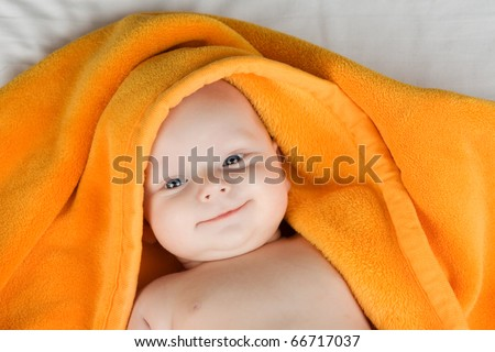 Portrait of smiling baby boy with towel covering head.