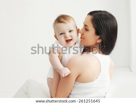 Portrait of smiling baby with mother at home in white room - stock photo
