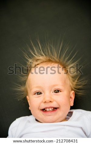 Portrait of smiling baby with standing hair from static electricity - stock photo