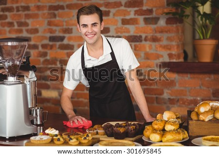 Portrait of smiling barista cleaning the counter at coffee shop - stock photo