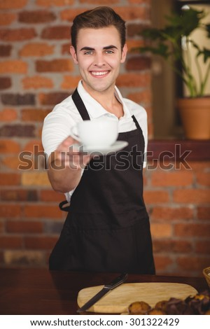 Portrait of smiling barista offering cup of coffee to camera at coffee shop