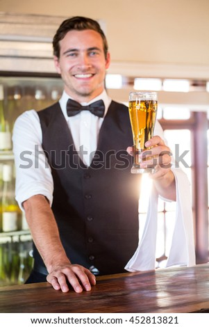 Portrait of smiling bartender standing at bar counter offering a glass of beer