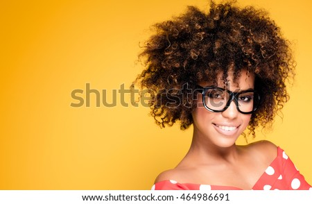 Portrait of smiling beautiful african american young woman. Girl with afro wearing eyeglasses. Yellow background. Studio shot.