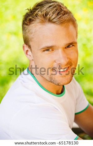 Portrait of smiling beautiful blonde young man on green natural background.