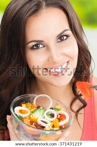 Portrait of smiling beautiful brunette woman eating salad, outdoors - stock photo