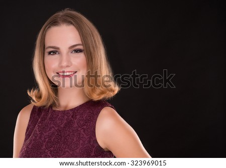 Portrait of smiling beautiful brunette woman on black background