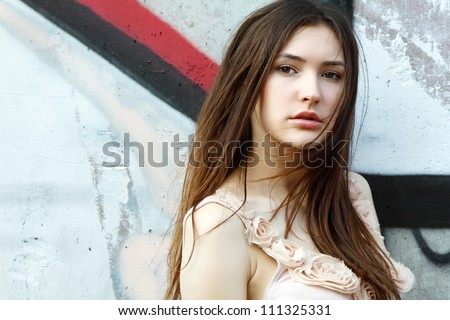 Portrait of smiling beautiful fashion girl against wall with abstract graffiti - stock photo
