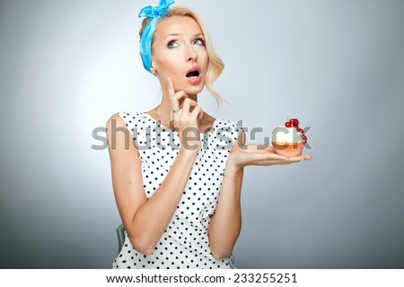 Portrait of smiling beautiful pinup woman. Girl holding sweet cake. - stock photo