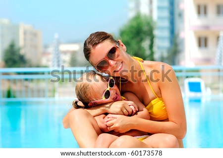 portrait of smiling beautiful woman and her little cute daughter in pool outdoor - stock photo
