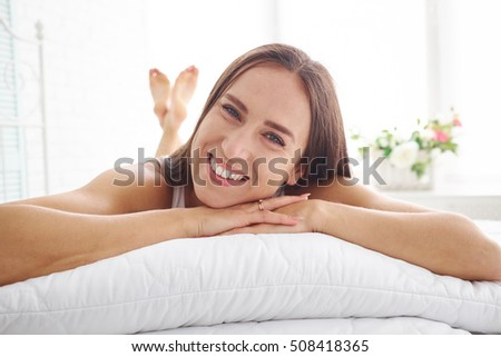 Portrait of smiling beautiful woman lying on bed with her hands resting on white pillow against sunlit window background