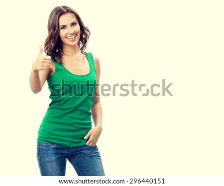 portrait of smiling beautiful young brunette woman showing thumbs up gesture, in smart green casual clothing, with blank copyspace area for slogan or text - stock photo